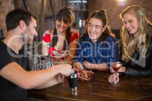 Friends looking at bartender making drinks in pub
