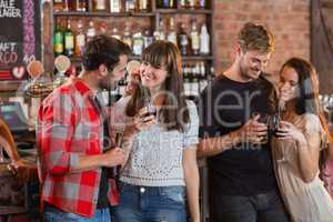 Young couples holding drinks in bar