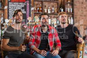 Shocked male friends looking away while holding beer bottles