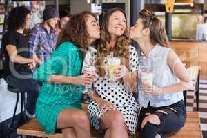 Female friends kissing woman in restaurant
