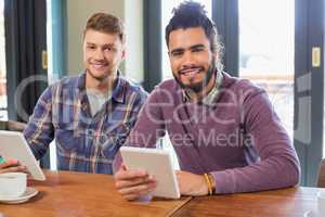 Male friends holding digital tablets in restaurant