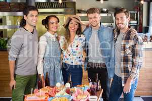 Happy friends standing by food and drink served on table in restaurant