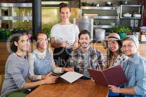 Smiling waitress and customers in restaurant