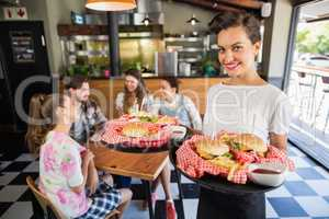 beautiful waitress serving burger to customers sitting in restaurant