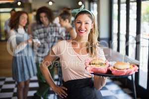Smiling young waitress serving burger in restaurant