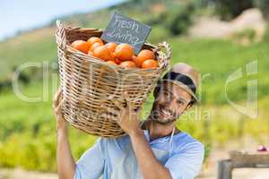 Portrait of smiling farmer carrying by fresh oranges in container