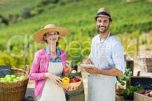 Happy couple holding bell peppers in basket with digital tablet