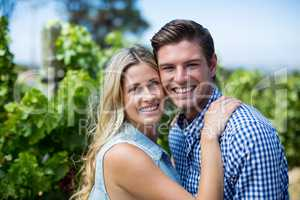 Portrait of smiling young couple hugging at vineyard