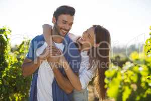Cheerful couple embracing at vineyard during sunny day