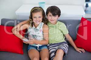 Sibling sitting on sofa with mobile phone in living room