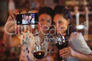 Young women taking a selfie from mobile phone while having a red wine