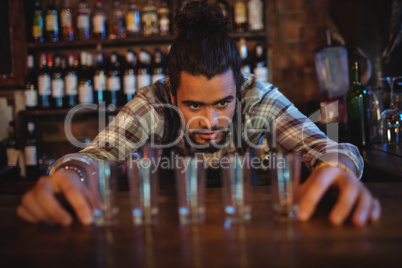 Waiter placing shot glasses on counter