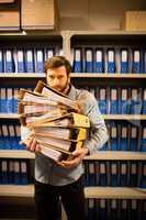 Worried businessman holding files in storage room
