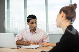Business people discussing contract during meeting