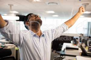 Cheerful businessman with arms raised at office