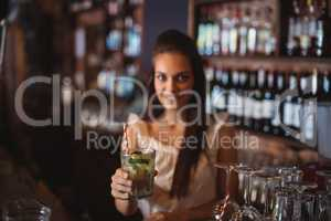 Portrait of female bar tender holding a glass of cocktail