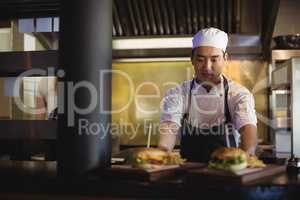 Chef placing tray with french fries and burger at order station