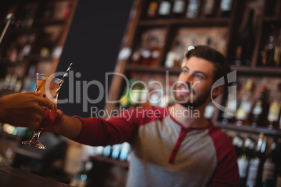 Female bar tender giving glass of cocktail to customer