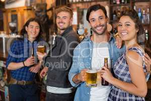 Portrait of friends with beer bottles and glasses in pub