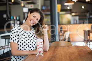 Portrait of young woman sitting by drink on table