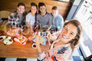 Portrait of woman photographing friends in restaurant