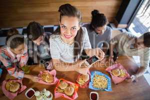 Young woman with friends photographing food in restaurant