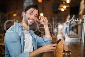 Young man using mobile while sitting at pub