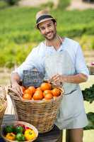Portrait of smiling farmer standing by fresh oranges in container