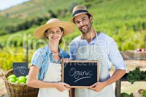 Portrait of happy couple holding chalkboard with text