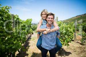 Portrait of smiling young couple piggybacking at vineyard