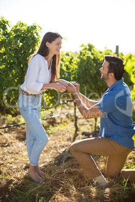 Happy young man proposing his girlfriend at vineyard