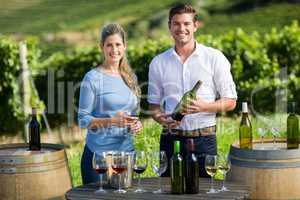 Portrait of friends holding wineglass and bottle by table against vineyard