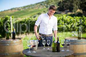 Smiling man pouring wine in glass on table