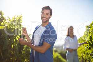 Happy couple standing by plants growing at vineyard