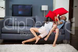 Siblings having pillow fight in living room