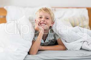 Portrait of smiling boy lying under bed sheet in bedroom