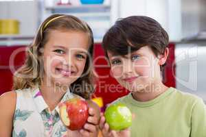 Siblings showing missing bite of apple in kitchen