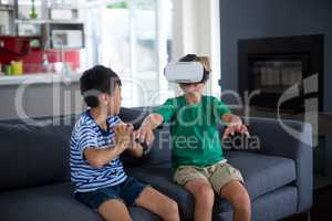 Boy looking at his brother using virtual reality headset in living room