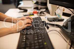 Cropped hands of businesswoman using computer keyboard at office