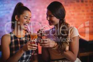 Two young women having cocktail drinks