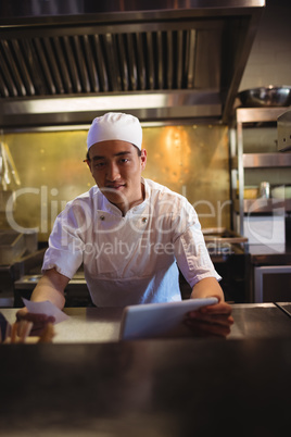 Chef holding digital tablet and an order list in the commercial kitchen