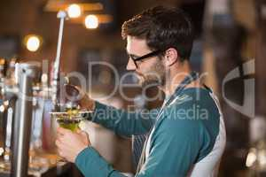 Side view of bartender making drinks while wearing eyeglasses