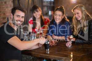 Portrait of handsome bartender making drinks for customers