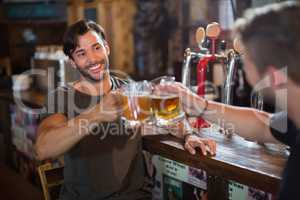 Smiling man toasting beer mug with male friend