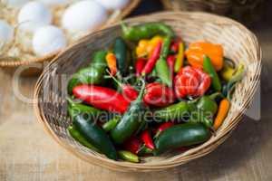 Bell peppers in wicker basket on table