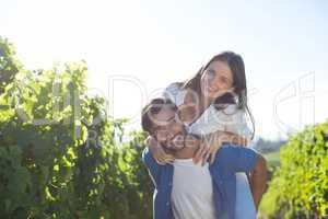 Happy young couple piggybacking during sunny day