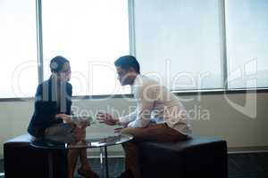 Business people discussing over digital tablet at office