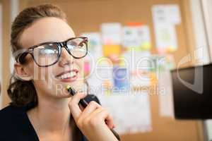 Thoughtful smiling businesswoman looking away in office