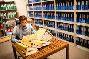 Businessman looking at stack of files on table in storage room