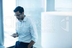 Young businessman using mobile phone while leaning on glass window